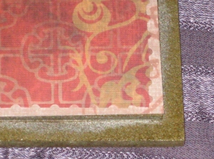 Layering paper onto the trivet tile. Here a light pink paper was cut to the size of the tile, and a dark pink paper was trimmed with fancy edge scissors and inset on top.  Both are applied to the trivet with Mod Podge.