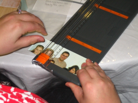 "This is a mom using a paper cutter to cut her photo into 2"" x 2"" squares."